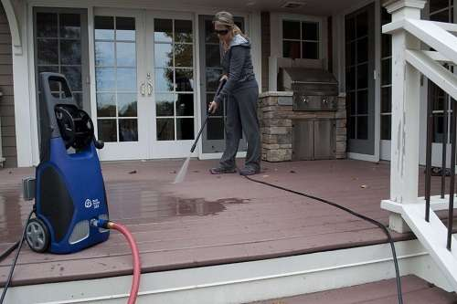 woman washing patio with a an electric pressure washer